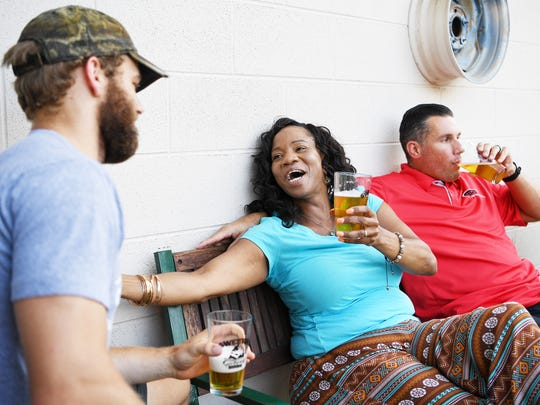 From left, Carey Blanton, Crystal Williams, and Brent Myers, sit outside at Sweeten Creek Brewing July 19, 2017.