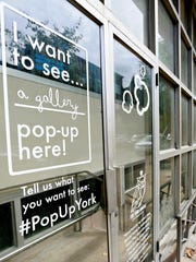 A #PopUpYork sign on a window at 1 North George Street