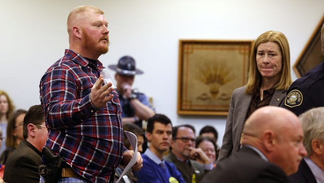 Casey Runyan, left, stands to object to the allowing of testimony of national gun control advocate Capt. Mark Kelly in front of the Senate Judiciary Committee at a public gun bill hearing in Hearing Room 50 Thursday Feb. 6, 2014. The hearing concerns a bill to expand background checks for firearms sales.