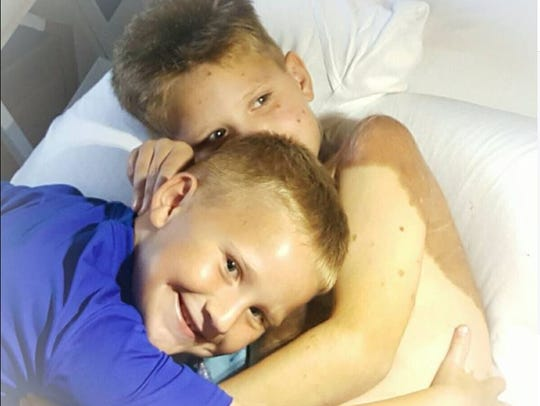 Charlie Denton is hugged by his brother, Beau Denton,