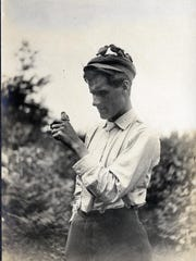 """A bush-tit feeds its young on top of a man's cap in a photo from the 1908 """"American Birds"""" book by William Lovell Finley. The photo is found opposite page 105. It is part of a digital project that is making 40 years of Oregon wildlife conservation photos and documents available to the general public."""