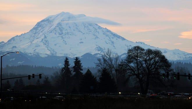 A clear-sky sunrise behind a snow-covered Mount Rainier.