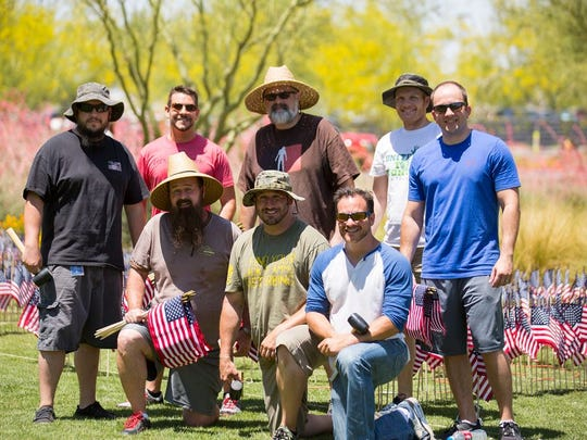 """Eight University of Phoenix employees, most with military affiliation, spelled out """"Salute to Sacrifice"""" with 10,000 mini American flags."""