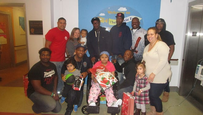 Members of the Paterson Bronze Heat Chapter of the International Association of Black Professional Firefighters visit children at the St. Joseph's hospital.