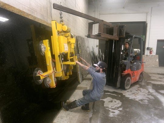 Alex Torres attaches suction cups to move a 1,200 pound slab of granite over to a cutting machine at Upstate Granite & Marble, Tile in Henrietta.