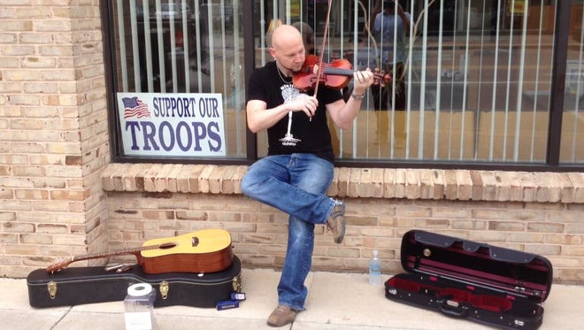 Jason Busse of the Fox Valley band Road Trip performs on College Avenue in downtown Appleton during the inaugural Street Music Week in 2013.