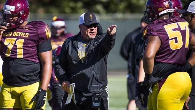 Special Teams Coordinator Shawn Slocum instructs offensive lineman Evan Goodman, right, during Arizona State University football practice, Wednesday, March 23, 2016.