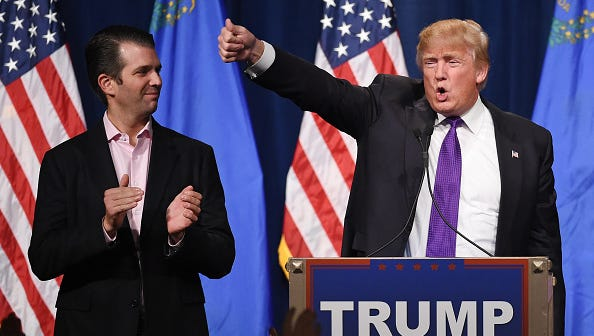 In this Feb. 23, 2016, file photo, Donald Trump Jr., left, looks on as his father, Republican presidential candidate Donald Trump, at a caucus night watch party in Las Vegas, Nevada. Donald TrumpJr. is this year's featured speaker at Faulkner University's annual Benefit Dinner.