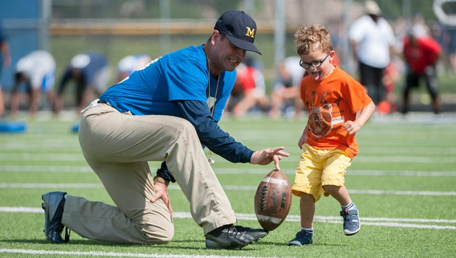 Michigan head football coach Jim Harbaugh goofs around with his son Jack Wednesday in Indianapolis.