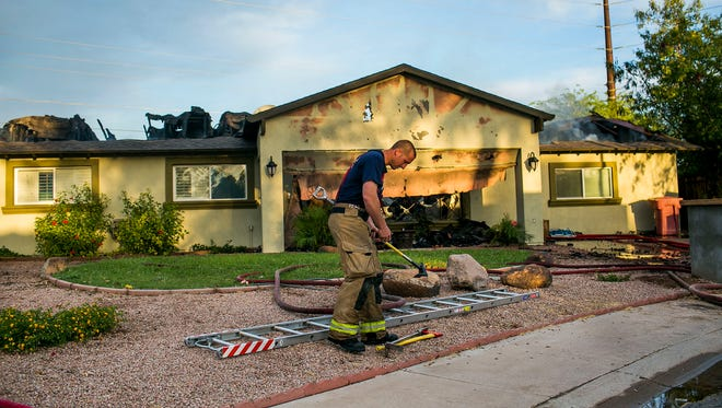 Firefighters worked to contain a fire that burned 2 houses in Scottsdale, Arizona on Friday, April 17, 2015.