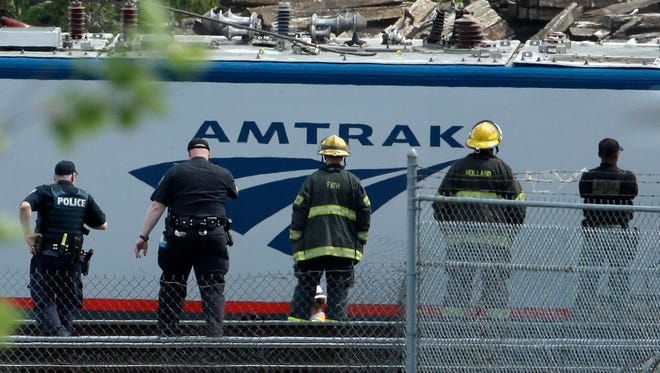 Emergency and transportation personnel work at the scene of a deadly train wreck, Wednesday, May 13, 2015 in Philadelphia. An Amtrak train headed to New York City derailed and crashed in Philadelphia on Tuesday night, May 12, 2015, killing at least seven people and injuring dozens more.