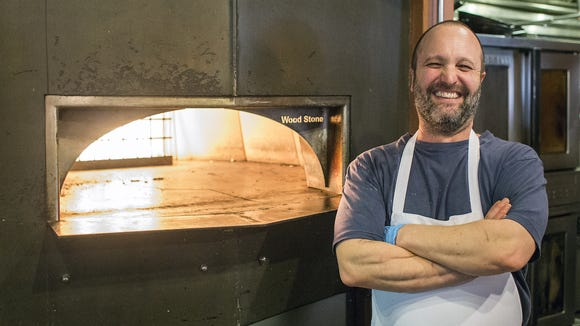 Nona Mia Italian Kitchen owner and chef Peter Affatato stands next to the widely used wood-fired oven in March.