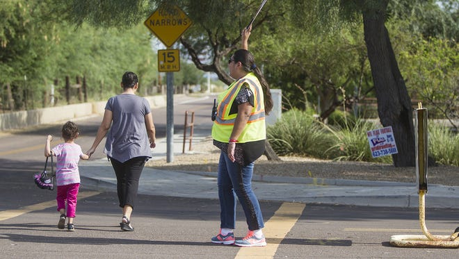 Nancy Munoz helps students and parents across the street before school starts at Desert Spirit Elementary School in Glendale on Wednesday, August 12, 2015. Munoz has been a crossing guard for six years.