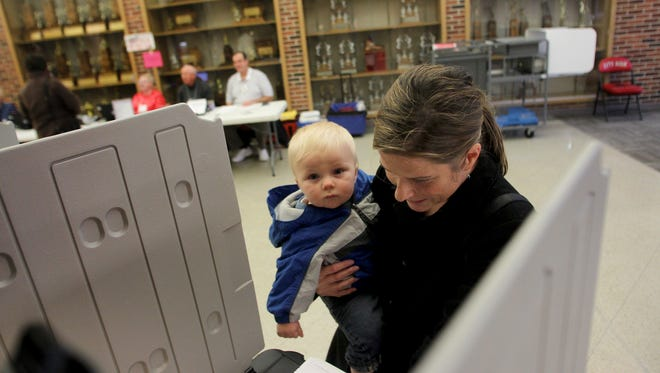 Mary Kate Hayek, wife of Mayor Matt Hayek, held her nine month-old son, Drew, while casting her vote at City High on election day in Iowa City on Tuesday, November 8, 2011.