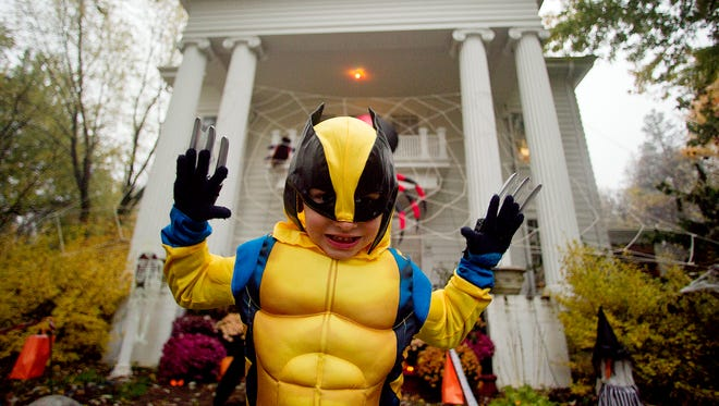 Brett Bennett, 5, poses as the X-man character Wolverine in front of his house on Fifth Avenue during trick-or-treating in Marshfield Thursday, Oct. 31, 2013.