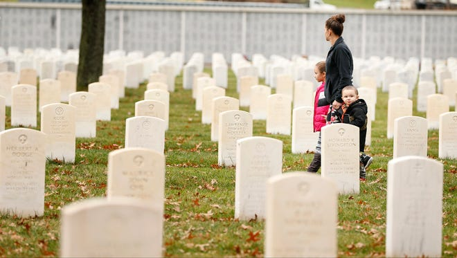 A family walks through the tombstones of veterans Wednesday following a Veteran Day ceremony at Woodlawn National Cemetery in Elmira.