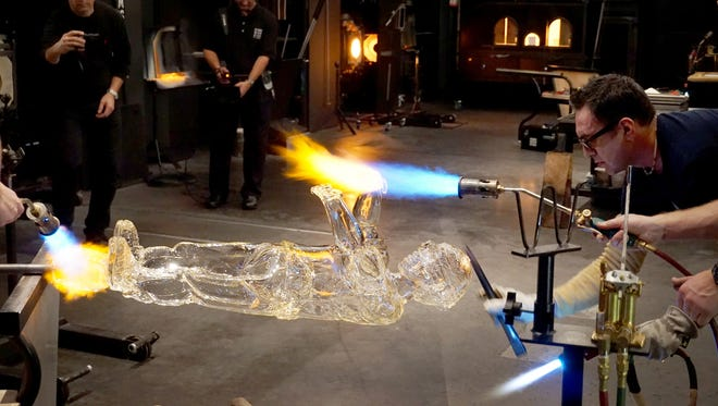 Guest artist Jaime Guerrero puts the finishing touch on his life-sized glass toddler at the Corning Museum of Glass' 2300 degree event Thursday. Guerrero sculpted the boy to be hitting a pi–ata; he will also make a bat and pi–ata.