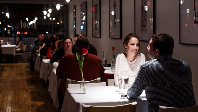 Amanda Carlton, laughs with husband Tom Carlton as they wait for their next course at Proof in Des Moines on Saturday, Feb. 13, 2016.