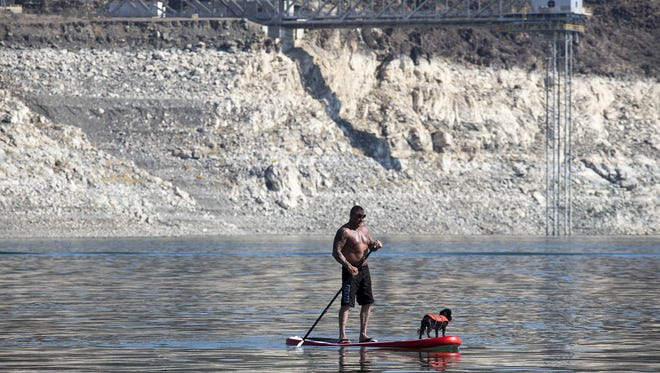 "Rick Cobler paddles with his dog near Lake Mead's Boulder Harbor in June 2015. A high-water mark, or ""œbathtub ring,""€ is visible on the shoreline."