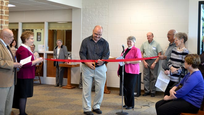 Dave Barnhart, chairman of the Building Committee, cuts the ribbon at Saint David's Lutheran Church's dedication ceremony.