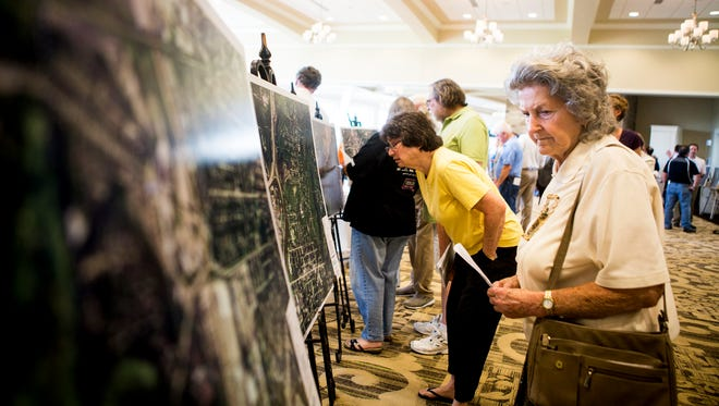 Dottie Delp, of Evendale, looks at maps at Duke Energy's public information meeting about the central corridor pipeline extension at Cooper Creek Event Center in Blue Ash Wednesday, June 15, 2016.