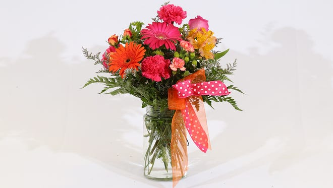 Patti Barclay's design features carnations, mini carnations, gerbera daisies, spray roses, alstromeria, limonium, hypericum berries, and greens (in hot pink, orange and lime-green) arranged in a large mason jar accented with hot pink, polka-dotted and orange ribbons.