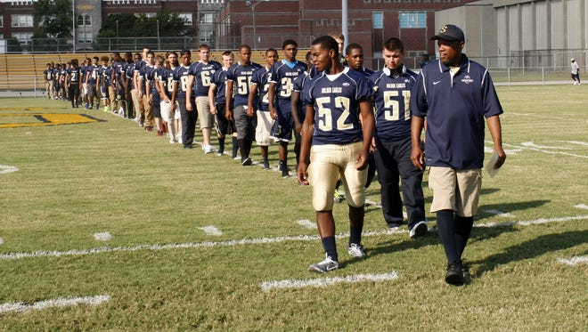 The 2013 Shawnee football team honors Daniel C. Lawson at the Academy at Shawnee during the dedication of the football field in honor of Lawson, who graduated from Shawnee High School in 1963.  Sept. 6, 2013