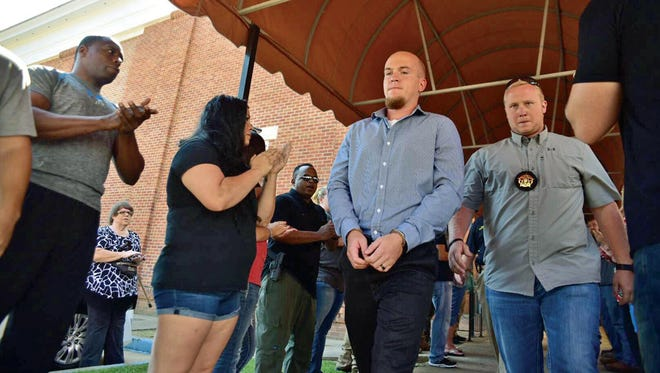 Former Columbus Police Department officer Canyon Boykin is led from the Lowndes County Courthouse Friday morning in handcuffs while onlookers applaud. Boykin was indicted on charges of manslaughter by a grand jury yesterday.