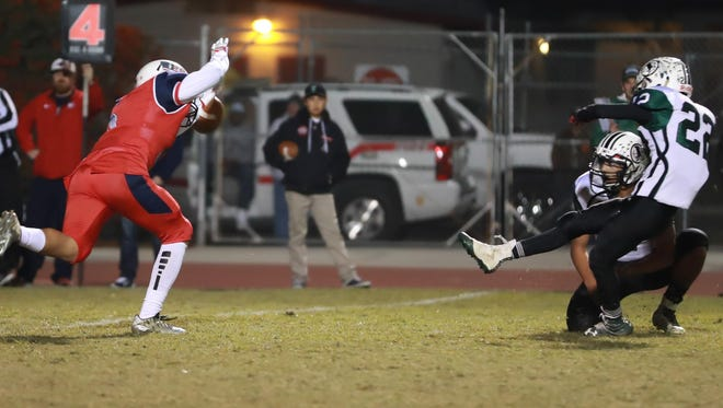 Tulare Western's Keshon Butler (5) blocks Tehachapi's field goal attempt late in the first half during a Central Section Division III quarterfinal playoff game at Bob Mathias Stadium. Tulare Western won 9-7.