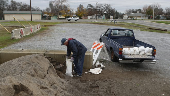 Jim Sinyard of Redding fills up sandbags Tuesday off Viking Way in preparation for upcoming heavy rain in the area.