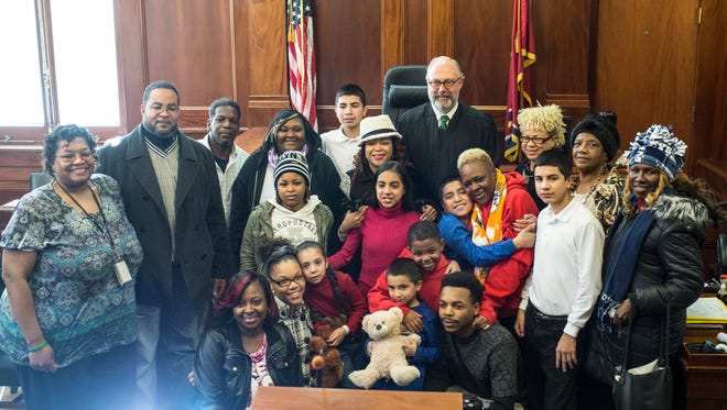 """Chancellor Jim Kyle, center, stands with Cora Savage along with her friends, family and newly adopted children during a Department of Child Services adoption ceremony, """"Home for the Holidays,"""" at the Judge D'Army Bailey Courthouse. Savage is taking the steps to adopt six brothers and sisters, ages 5-13, keeping them together and creating a new family. I met Savage for the first time that day through David Waters, who was working on his column for the newspaper. Seeing her with the kids and seeing the way they looked up at her, it was easy to tell the kind of person she is. It takes a special kind to adopt.  Witnessing not only Savage, but families that adopted a total of 13 children just before the holidays affirms the joy that comes from caring for people.  The """"1,000 Words"""" feature is a pictorial commentary on events in Greater Memphis and around the world. Today's """"1,000 Words"""" was written by Brad Vest, a photographer for The Commercial Appeal."""