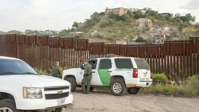 U.S. Border Patrol agents patrol the border fence in Nogales, Ariz.