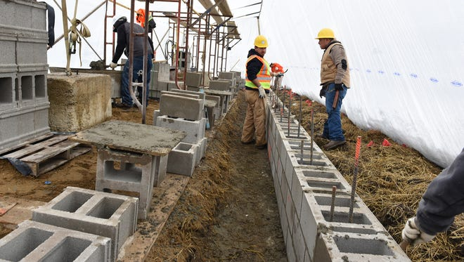 A crew from Agazzi Development works on the foundation and walls of the South Lyon Hotel on Jan. 31.