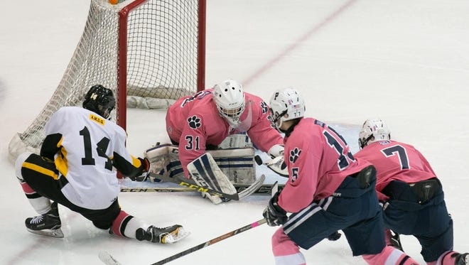 Pittsford goalie William Hernes makes a save with McQuaid forward Alex Spoto at the doorstep during the annual Pink the Rink game at RIT's Gene Polisseni Center in Henrietta on Saturday, February 4, 2017.