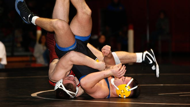 Woodbrige's Bryan McLaughlin (left) and Cranford's Vince Concina  wrestle at 170 pounds during the District 14 finals on Saturday at Woodbridge.