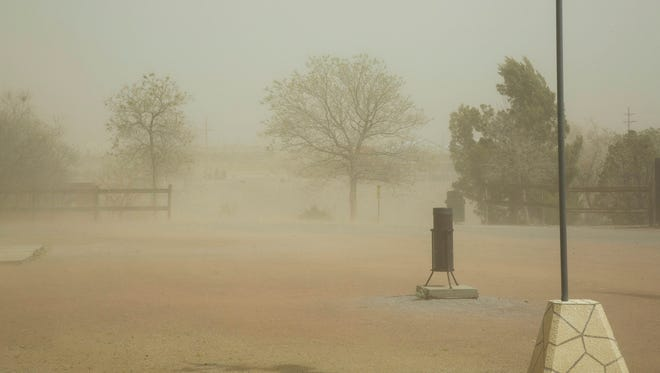 This photo taken March 23, 2017, shows sustained 43 mile per hour winds with 58 mile per hour gusts picked up dust obscuring both the Organ Mountains and A Mountain from view at the New Mexico Farm and Ranch Heritage Museum in Las Cruces, N.M.  Not unlike a flash mob gathering in a public place to briefly capture the attention of unsuspecting passers-by, the ingredients in this case — warm temperatures and a lack of rain — came together quickly in New Mexico. It's called a flash drought.