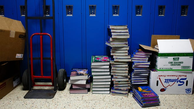 Textbooks that are only a few years old sit stacked next to lockers on the last day of the high school at Charter Oak-Ute School on Wednesday, May 31, 2017, in Charter Oak. The books will try to be resold before being thrown out.