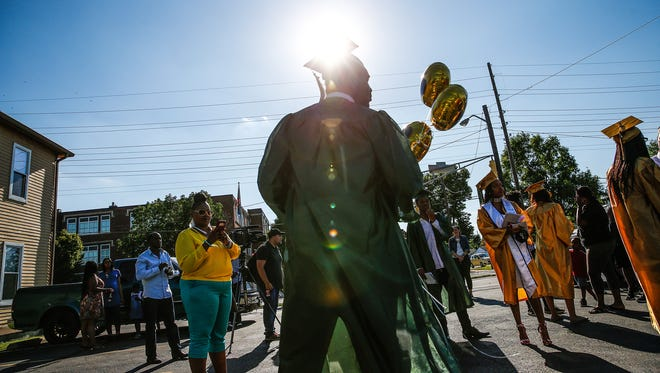 Crispus Attucks student Shandon Boyd, barred from his graduation due to his participation in a prank at the school, waits across the street as the rest of his classmates make their way inside for their graduation ceremony on Thursday, June 8, 2017.