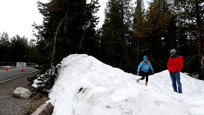 Jonathan Frank and his daughter Mei Ling, 11, play in snow Monday near the gate that closes the road running through Lassen Volcanic National Park.