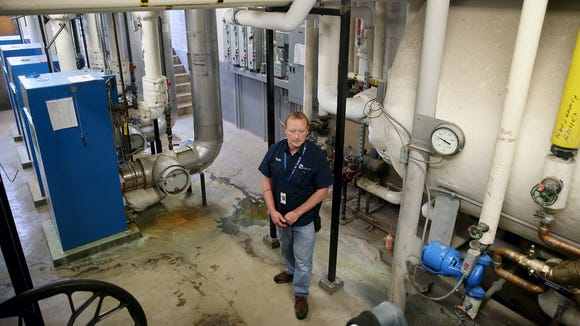 "Central Kitsap School District electrician Ryan Watland in the aging boiler room of Central Kitsap Middle School. The school is slated for demolition and replacement, and the new middle school set to open in 2019 will meet ""high performance"" standards for air quality."