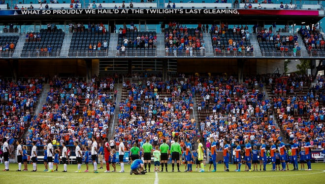 FC Cincinnati and Charleston Battery line up on the pitch for the national anthem at Nippert Stadium in Cincinnati on Saturday, June 17, 2017.