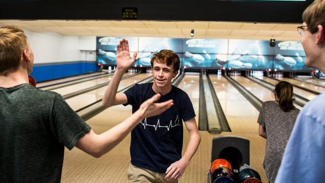 Jimmy Morrow, center, high fives William Moody after scoring a strike during the Take Back Our Alley event at Billy Hardwick's All Star Lanes in February 2017 in Memphis.