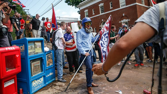 A white nationalist prepares to swing his flag stick and use makeshift shields to help push his crews way through counter protesters at Emancipation Park during the 'Unite the Right' rally in Charlottesville on Saturday, August 12, 2017.