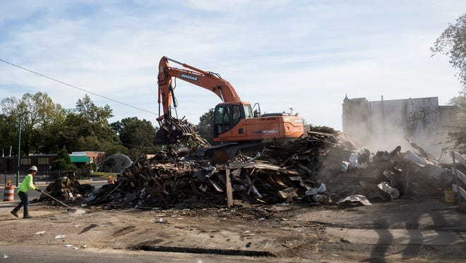 October 19, 2017 - A backhoe demolishes two structures on a prominent Midtown corner to clear the way for a small, mixed-use development. Taylor Caruthers bought the old buildings on about a quarter-acre in April for $275,000, property records show. He plans to build there a mixed-use development with retail or restaurant on the ground floor with apartments above.