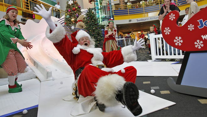 Santa lands at the bottom after sliding down the Jolly Days slide to officially start the holiday season and Jolly Days at The Children's Museum of Indianapolis, Friday, November 23, 2012. Kelly Wilkinson / The Star