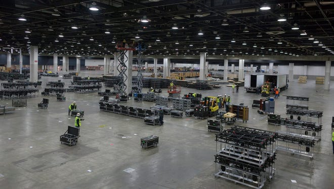 Workers begin the installation of lighting trusses for the North American International Auto Show 2018 at Cobo Center in Detroit.