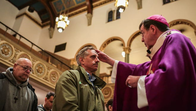 Archbishop Allen Vigneron of the Archdiocese of Detroit places ashes on Dave Guastella, of Canton, Mich., during Ash Wednesday service at St. Aloysius Church in Detroit on March 1, 2017.