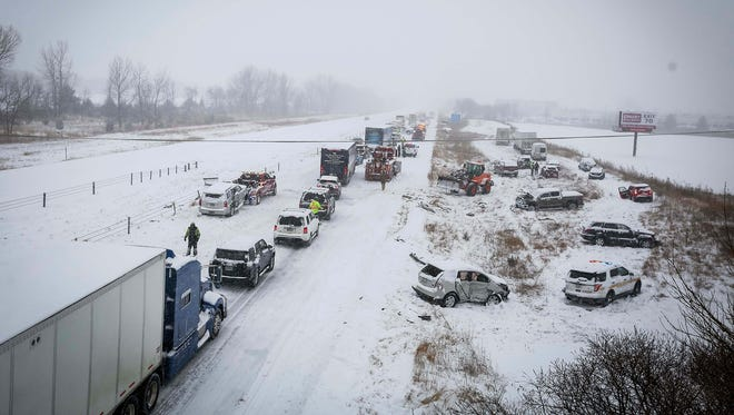 Officials work on cleaning up a 7-vehicle pileup on  Interstate 35 southbound in Ames, Iowa, on Monday, Feb. 5, 2018. One person was killed.