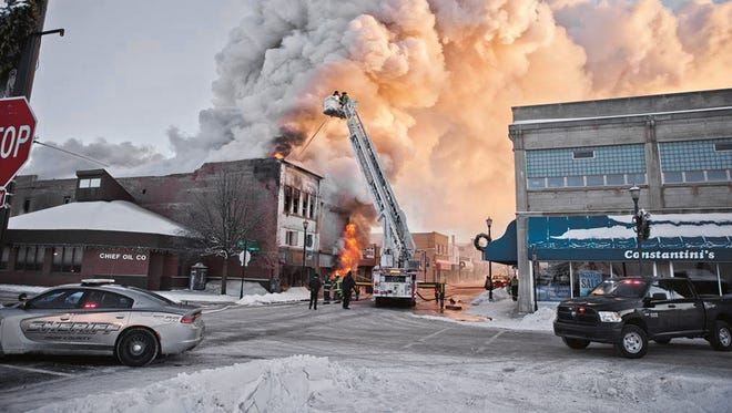 Firefighters battle a fire in downtown Ironwood, Mich., Wednesday, Feb. 21, 2018. The fire claimed at least one life and destroyed two buildings. One of the buildings included two floors of apartments. As of noon, public safety officials wouldn't comment on other injuries, but were working to account for everyone. The cause of the fire remains under investigation.