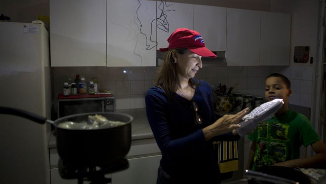 Michelle Rebollo cooks dinner in her kitchen by solar and battery-powered light, using a propane camp stove in Toa Alta, Puerto Rico after a major power outage hit the island earlier that day, March 1, 2018.